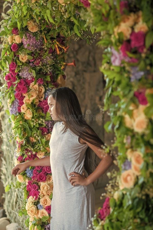 Jugendliche mit langem Haarstand im Blumenbogen, Schönheit stockbild