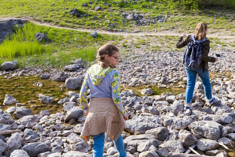 Jugendliche mit Rucksäcken kreuzen vorsichtig The Creek entlang den Felsen und wandern in die Waldsommerferien stockfotos
