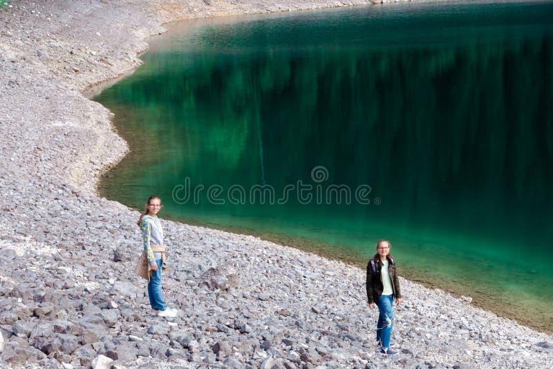 Jugendliche stehen auf Steinen auf der Bank des Sees, der den Wald reflektiert und wandern in den Waldsommerferien stockfotos