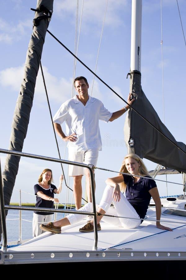 Jugendliche und Muttergesellschaft auf Segelboot am Dock stockfotos