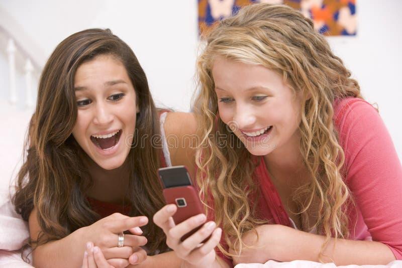 Jugendlichen, die auf Bett unter Verwendung des Handys liegen stockbilder