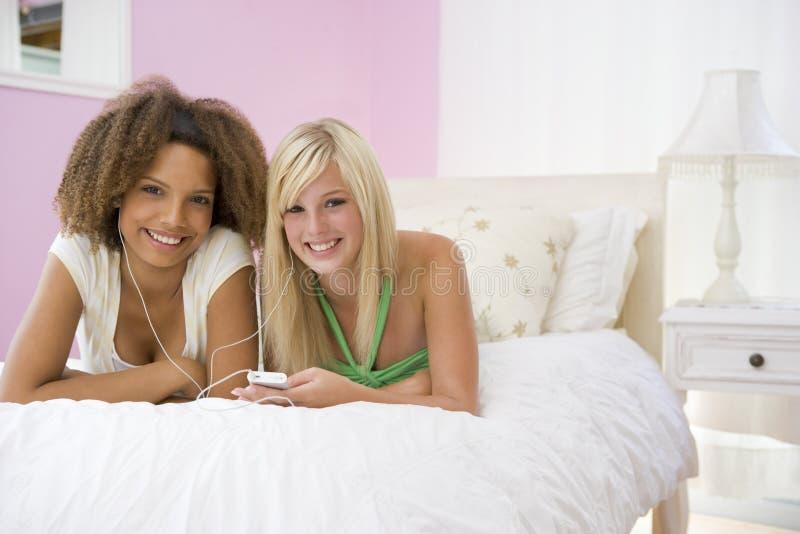 Jugendlichen, die auf dem Bett hört zum MP3-Player liegen lizenzfreie stockfotos