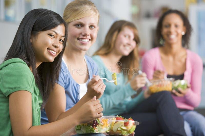 Jugendlichen, welche zusammen die gesunden Mittagessen genießen stockfotos