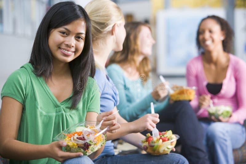 Jugendlichen, welche zusammen die gesunden Mittagessen genießen lizenzfreies stockbild