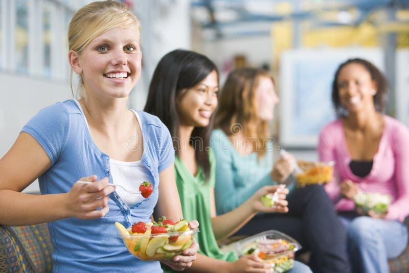 Jugendlichen, welche zusammen die gesunden Mittagessen genießen lizenzfreie stockfotos
