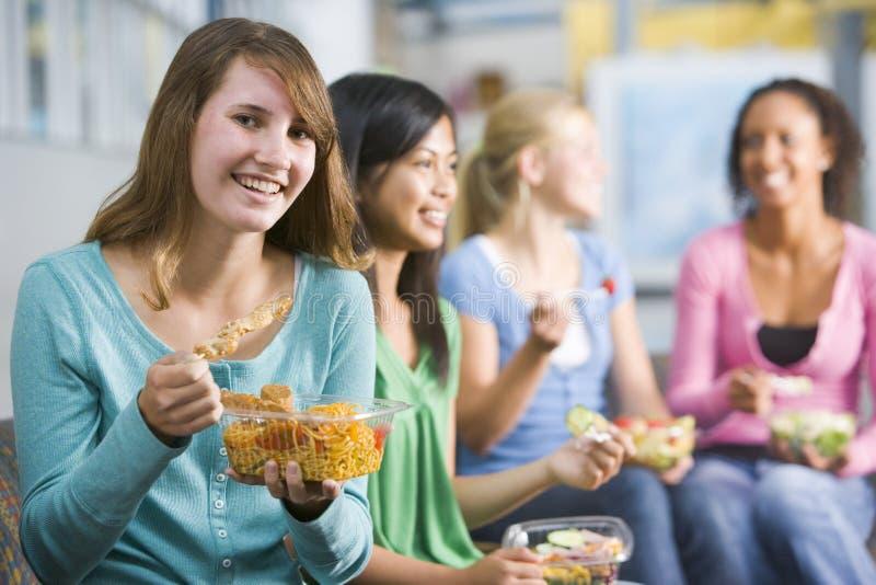 Jugendlichen, welche zusammen die gesunden Mittagessen genießen lizenzfreie stockbilder