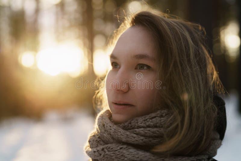 Jugendlicheporträt im Winterkiefernwald ist Sonnenuntergang lizenzfreie stockbilder