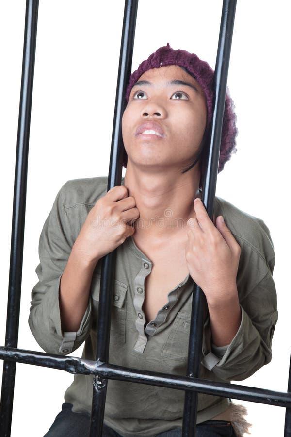 Jugendlicher Delinquent hinter Stäben lizenzfreies stockfoto