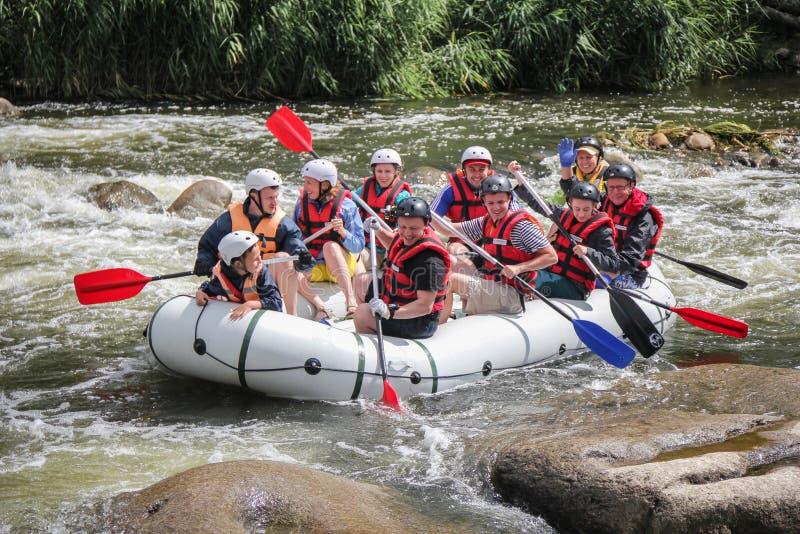 Jugendlicher, der auf dem Fluss-, Extrem- und Spaßsport an der Touristenattraktion flößt Flößen auf stockfotografie