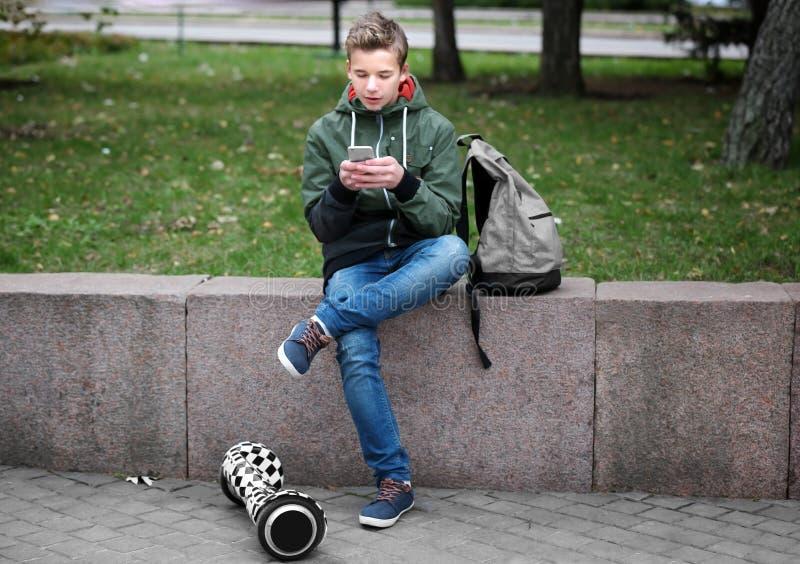Jugendlicher, der auf Geländer mit Handy sitzt lizenzfreie stockbilder