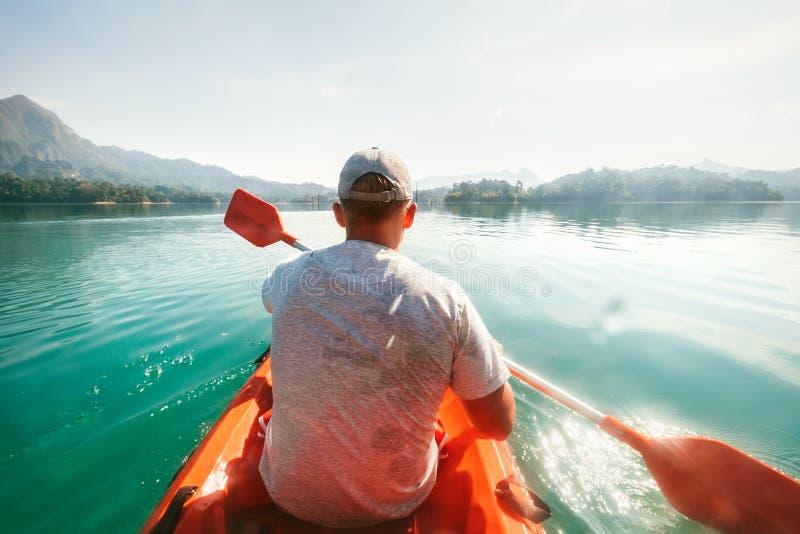 Jugendlicher, der auf Kajak auf ruhigem Wasser auf Cheow Lan Lake, Nationalpark Khao Sok, Thailand schwimmt lizenzfreie stockbilder