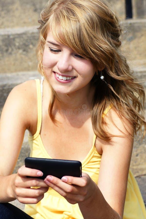 Jugendlicher, der auf Mobile oder Handy texting ist stockbild