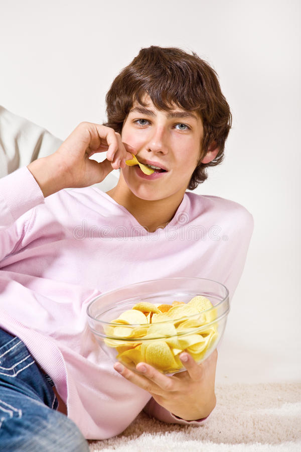 Jugendlicher, der Chipsletten isst stockbilder