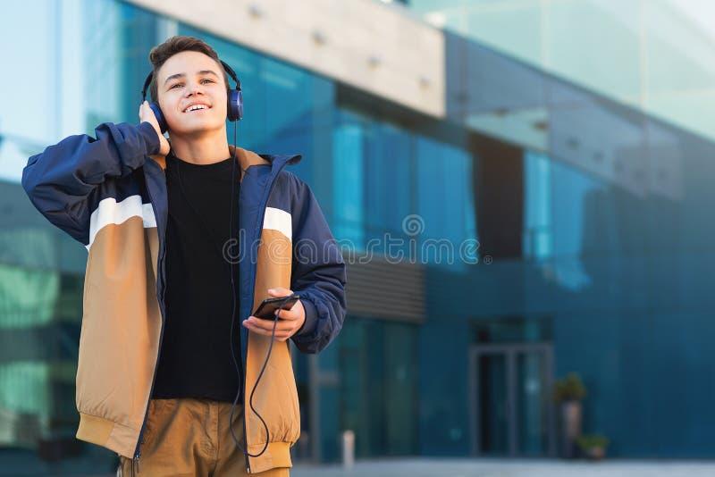 Jugendlicher, der das Hören Musik, das Telefon draußen halten genießt Kopieren Sie Platz stockbilder
