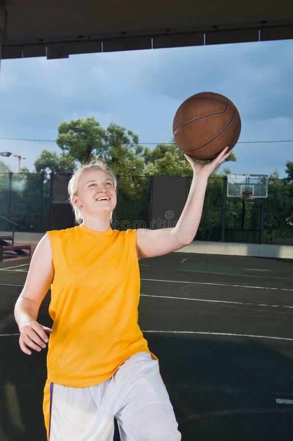Jugendlicher, der die Basketballfelge in Angriff nimmt stockbild