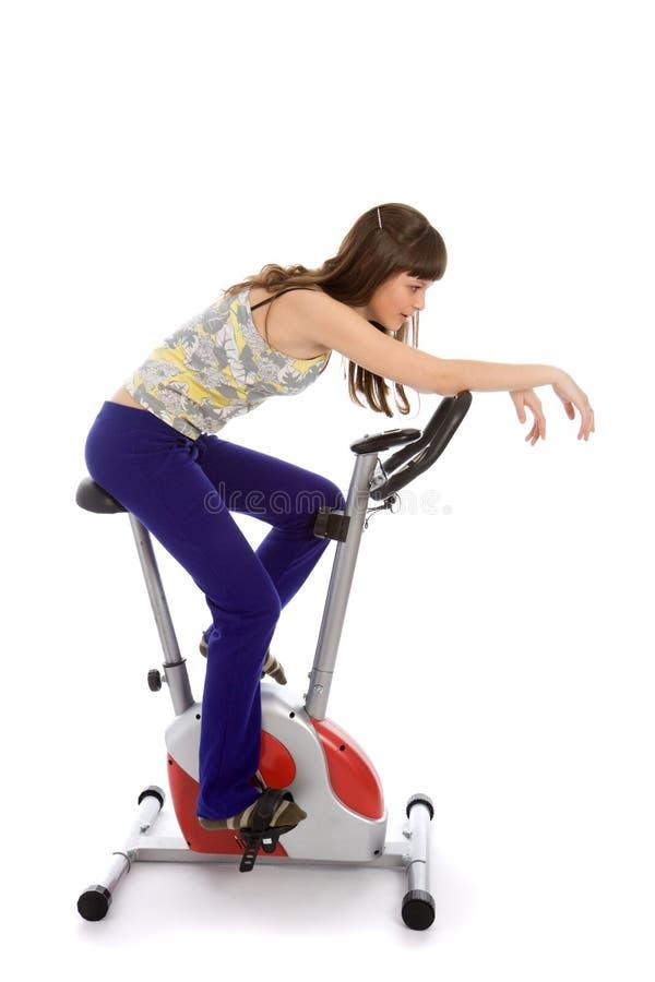Jugendlicher, der Eignung auf einem stationären Fahrrad tut stockbild