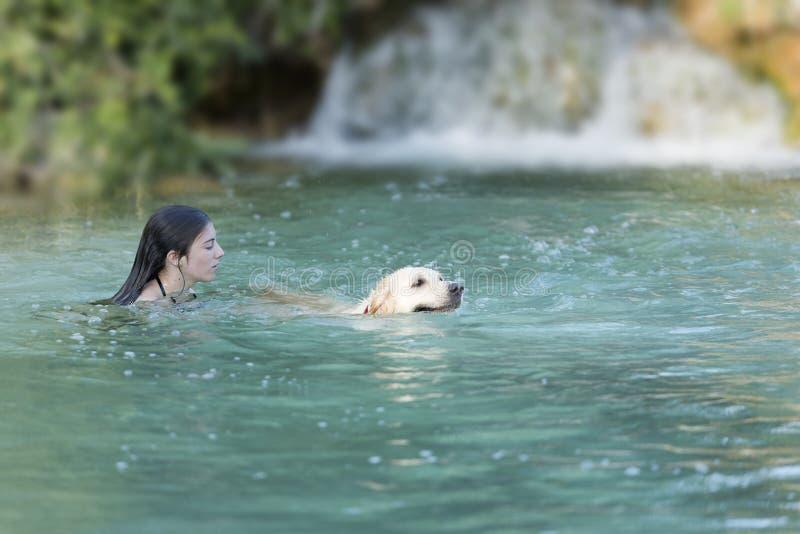 Jugendlicher, der in einem See mit ihrem Hund badet lizenzfreie stockbilder