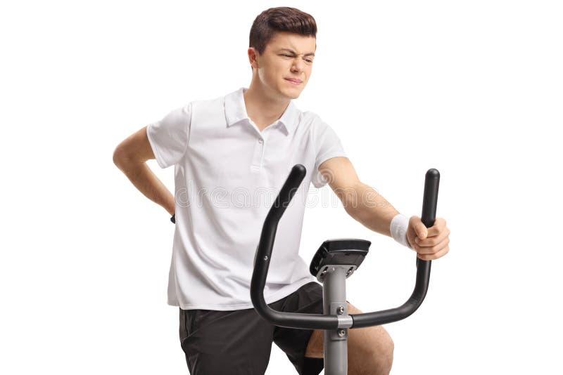 Jugendlicher, der einen Hometrainer reitet und Rückenschmerzen erfährt stockbild