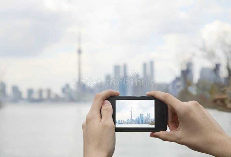 Jugendlicher, der Foto die schöne Skylineansicht von Toronto-Stadtzentrum mit Handy vertritt stockbild