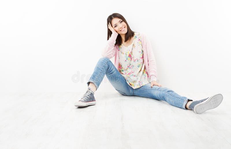 Jugendlicher der jungen Frau in den Jeans, die auf weißem Boden sitzen stockfotografie