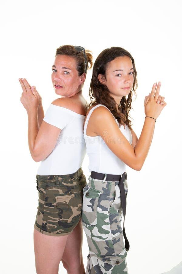 Jugendlicher der jungen Frau und ihre Mutter zurück zu hinterem Spiel mit Fingergestengewehr wie Film lizenzfreies stockfoto