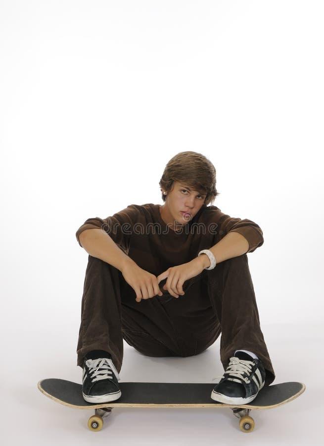 Jugendlicher, der mit Füßen auf Skateboard sitzt lizenzfreie stockfotos