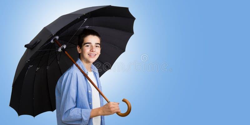 Jugendlicher, der mit offenem Regenschirm lächelt lizenzfreies stockbild