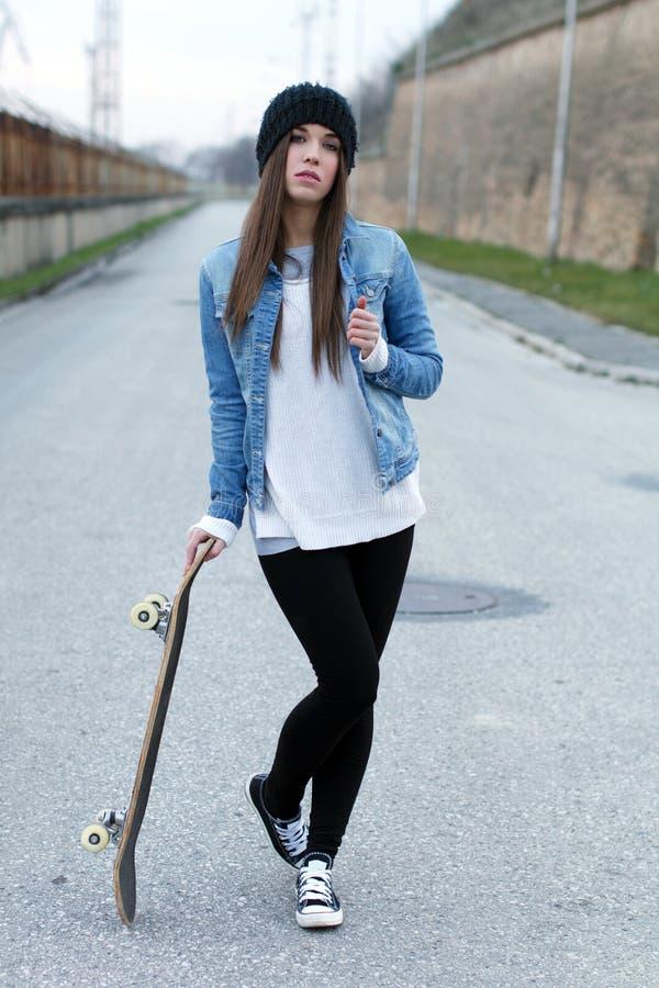 Jugendlicher, der mit Skateboard aufwirft lizenzfreies stockbild