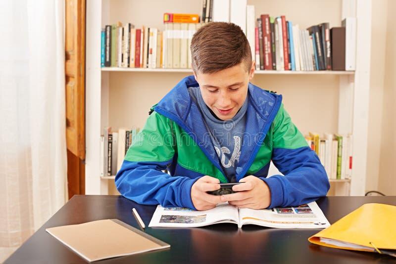 Jugendlicher, der mit Smartphone beim Studieren simst stockbilder