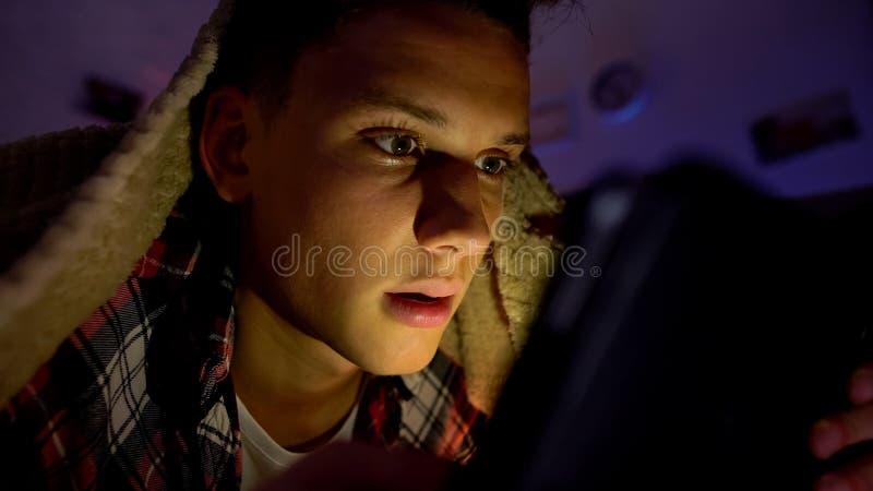 Jugendlicher, der unter Decke liegt und Spiel auf Tablette, Ger?tsucht spielt lizenzfreies stockbild