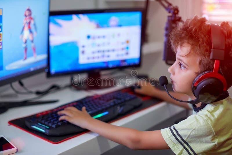 Jugendlicher, der zu Hause Computer, Spielspiel in seinem Kinderraum verwendet lizenzfreie stockfotos
