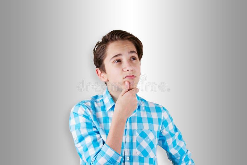 Jugendlicher, der zweifelhaft ist oder an etwas denkt lizenzfreie stockfotografie