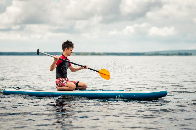 Jugendlicher in einem Taucheranzug schwimmt, ein supsurf auf dem See sitzend stockbilder