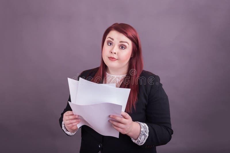 Jugendlicher Geschäftsfrau-Holdingstapel Papiere, die Blick auf ihrem Gesicht infrage stellen lizenzfreie stockfotografie