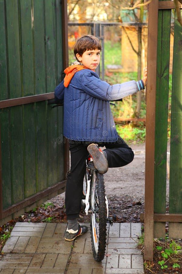 Jugendlicher hübscher Bauernjunge mit dem Fahrrad bereit zu reiten stockfotografie