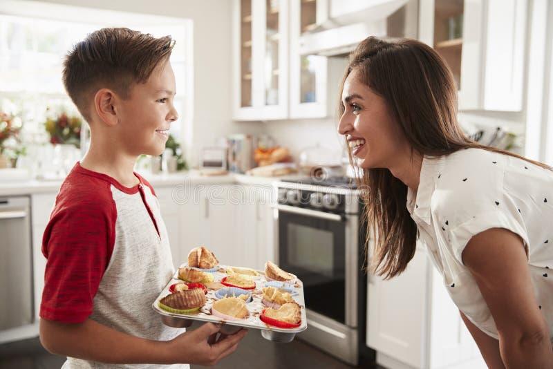 Jugendlicher hispanischer Junge, der die Kuchen darstellt, die, er zu seiner stolzen Mutter gebacken hat, Abschluss oben stockfotografie