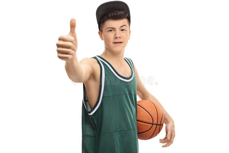 Jugendlicher im grünen Trikot mit Basketball und dem Daumen oben lizenzfreie stockfotos