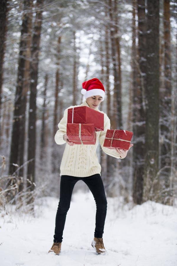 Jugendlicher im Hut Santa Claus sammelt Geschenke in einem schneebedeckten Wald herein lizenzfreies stockbild