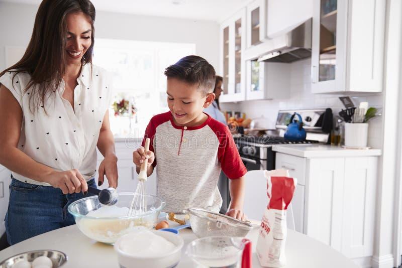 Jugendlicher Junge, der einen Kuchen in der Küche mit seiner Mama, Abschluss oben macht lizenzfreie stockbilder