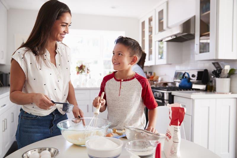 Jugendlicher Junge, der einen Kuchen in der Küche mit seiner Mama, einander betrachtend, nah oben macht lizenzfreie stockbilder