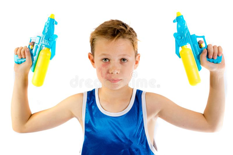 Jugendlicher Junge, der mit Wasserwerfern spielt stockfotos