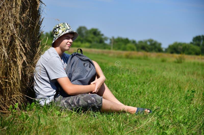 Jugendlicher mit dem Rucksack, der nahe bei Stapel Stroh sitzt lizenzfreie stockbilder