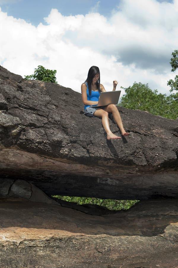 Jugendlicher mit Laptop sitzt auf Felsen lizenzfreies stockfoto