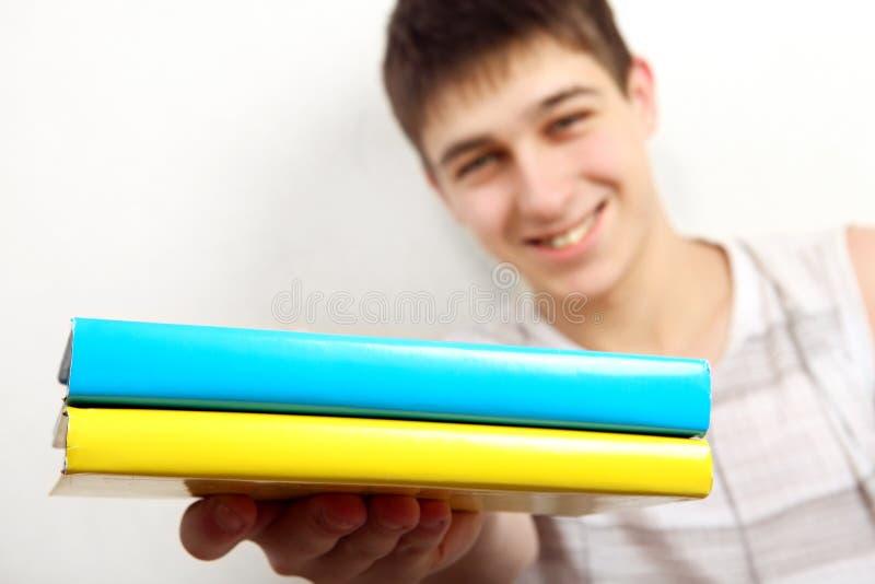Jugendlicher mit zwei Büchern stockbild