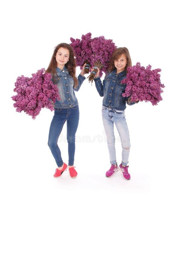 Jugendlicher mit zwei Mädchen, der mit Flieder in den Händen steht stockfoto