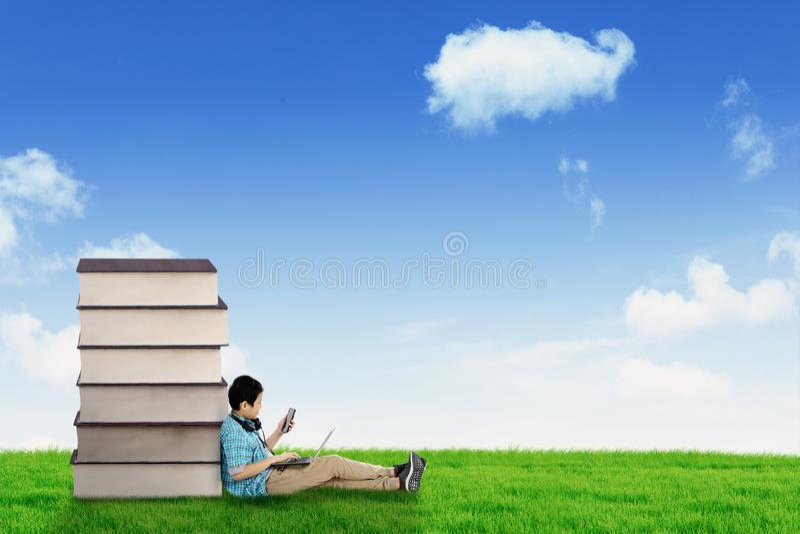 Jugendlicher Schüler sitzt nahe Büchern in der Wiese lizenzfreie stockbilder