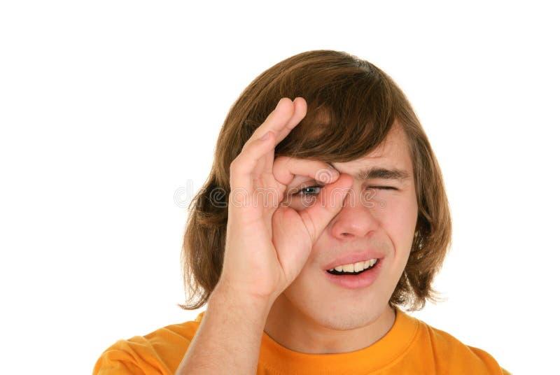 Jugendlicher schaut durch Ring von den Fingern stockfotografie