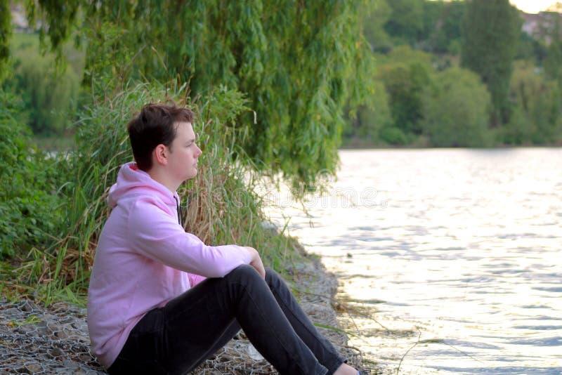 Jugendlicher sitzt am water& x27; s-Rand mit einer rosa Strickjacke und Vegetationen stockfotos