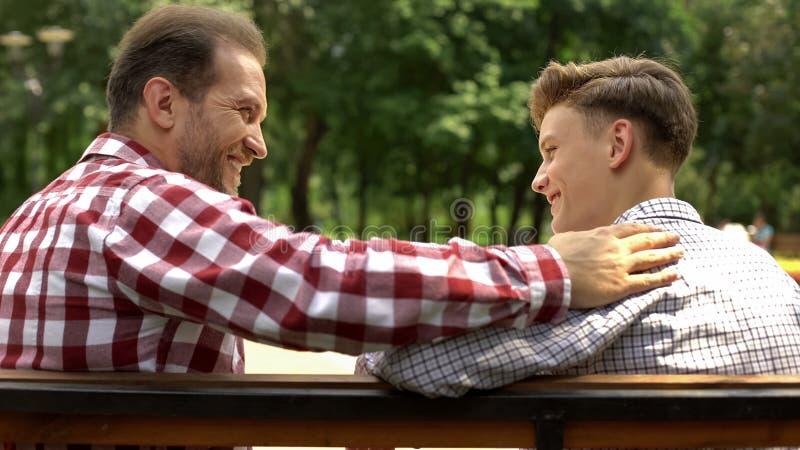 Jugendlicher Sohn, der mit Vater auf Bank im Park, Vati stützt sein Kind spricht lizenzfreies stockfoto