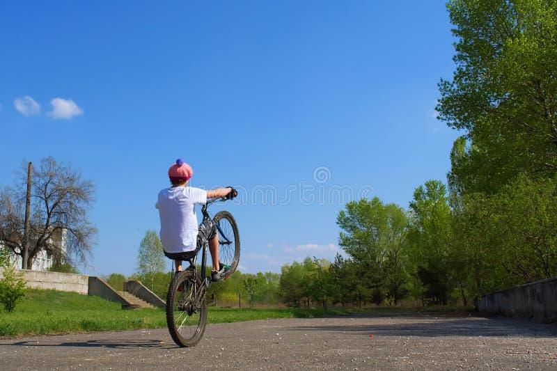 Jugendlicher springt auf Fahrrad stockbild